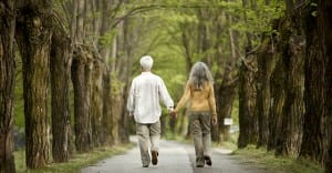 man and woman holding hands and walking down road