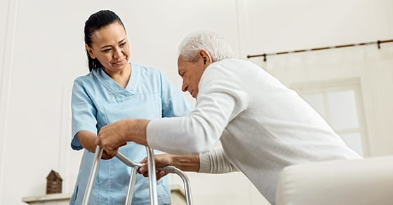 nurse helping elder man with walker | Consider Tax-Qualified Long-Term Care Insurance  | Dalby, Wendland & Co, P.C. | CPAs | Trust, Estate and Gift Tax Planning | Grand Junction CO | Glenwood Springs Co | Montrose CO